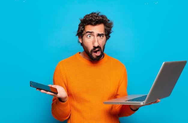 Junger bärtiger mann, der einen laptop hält. social-media-konzept