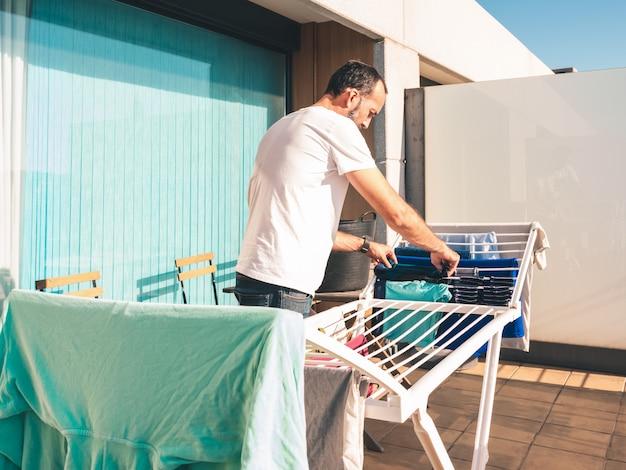 Junger bärtiger mann, der einige blaue hosen auf der terrasse seines dachbodens heraushängt