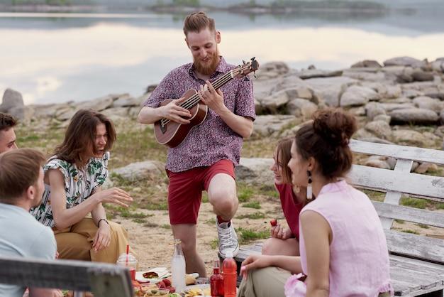 Junger bärtiger mann, der gitarre spielt und freudig lächelt, während er mit freunden in der nähe des sees rumhängt, um tisch sitzt, isst und spricht