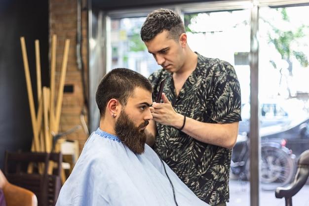 Junger bärtiger mann, der haarschnitt durch friseur erhält, während im stuhl am friseursalon sitzt