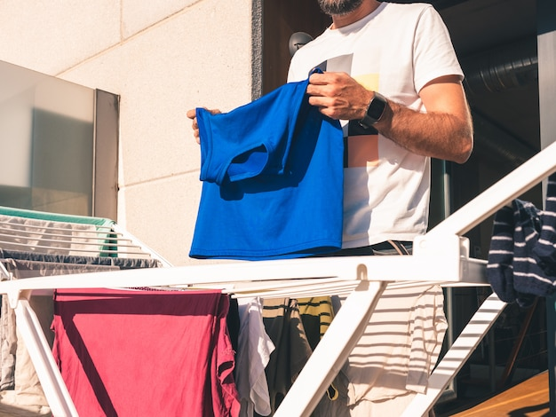 Junger bärtiger mann, der heraus blaues t-shirt auf der terrasse seines dachbodens hängt