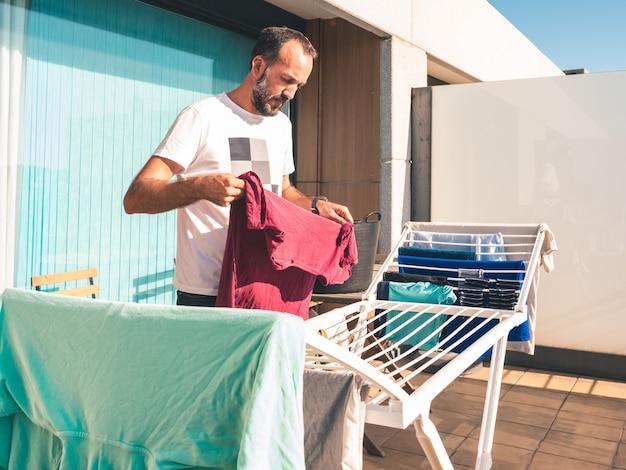 Junger bärtiger mann, der heraus rotes t-shirt auf der terrasse seines dachbodens hängt