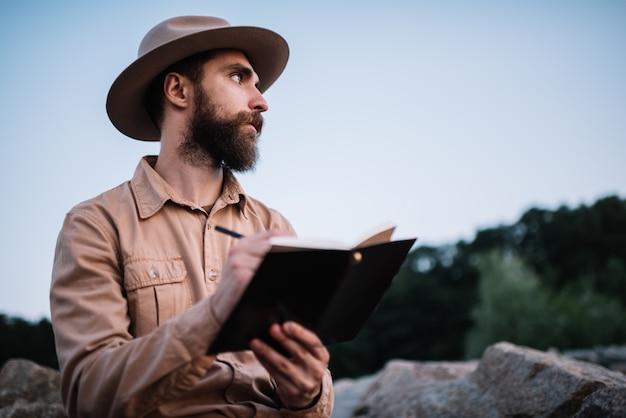 Junger bärtiger mann, der hipsterhut trägt, der notizen im notizblock schreibt und reise plant