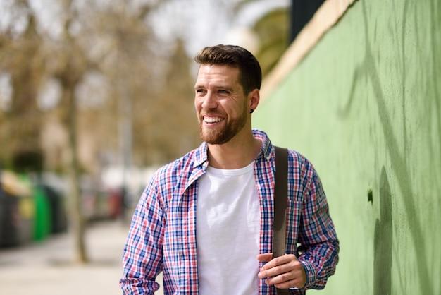 Junger bärtiger mann, der im städtischen hintergrund lächelt. lifestyle-konzept.