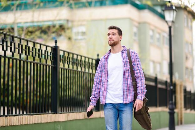 Junger bärtiger mann, der in städtischen hintergrund geht. lifestyle-konzept.