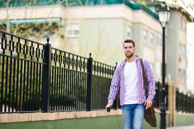 Junger bärtiger mann, der in städtischen hintergrund geht. lifestyle-konzept