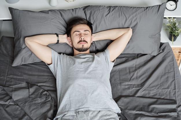 Junger bärtiger mann, der mit den händen hinter dem kopf liegt, während er allein im bett schläft