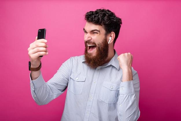 Junger bärtiger mann, der mit einer hand eine gewinnergeste macht, während er auf sein telefon schaut, schreit und ohrstöpsel trägt.