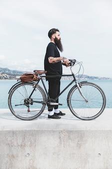 Junger bärtiger mann, der mit fahrrad auf wellenbrecher steht