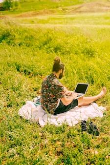 Junger bärtiger mann, der mit laptop auf dem gebiet sitzt