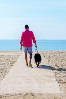 Junger bärtiger mann, der mit seinem hund am strand gefesselt geht