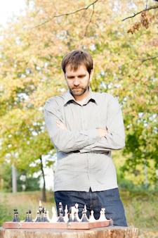 Junger bärtiger mann, der mit verschränkten armen über einem schachbrett im freien steht und über seinen nächsten schachzug nachdenkt