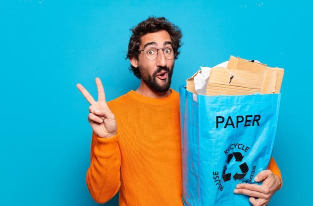Junger bärtiger mann, der papiertüte holt. recycling-konzept Premium Fotos