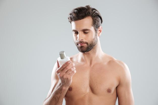 Junger bärtiger mann, der parfüm betrachtet