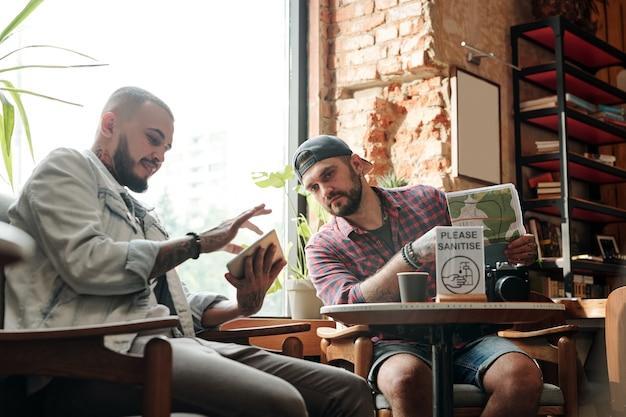 Junger bärtiger mann, der reise-app auf tablette verwendet, während reise zusammen mit freund im dachbodencafé plant