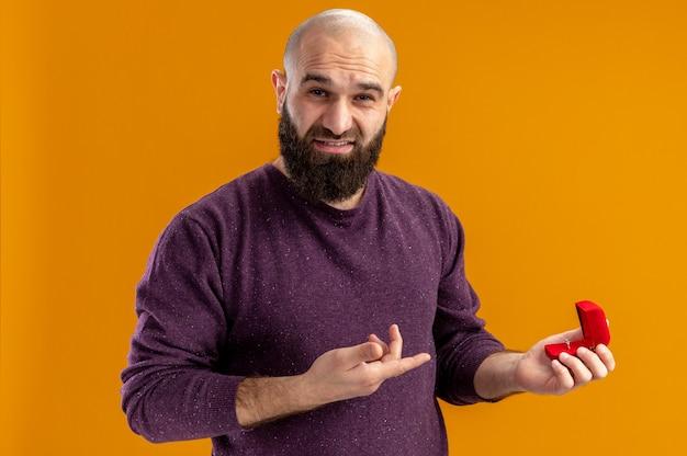 Junger bärtiger mann, der rote box mit verlobungsring hält, der mit zeigefinger darauf schaut und kamera mit skeptischem ausdruck valentinstagkonzept betrachtet, das über orange wand steht