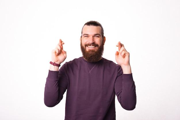 Junger bärtiger mann, der seine hände mit gekreuzten fingern hält und hofft, dass sein traum wahr wird