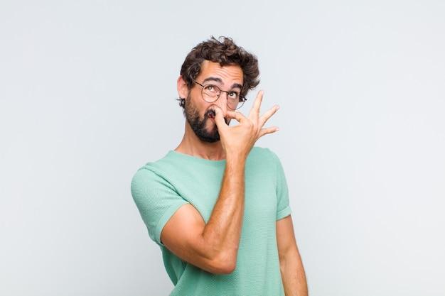 Junger bärtiger mann, der sich angewidert fühlt und die nase hält, um einen üblen und unangenehmen gestank zu vermeiden