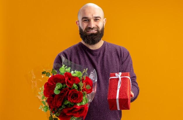 Junger bärtiger mann, der strauß der roten rosen und ein geschenk des lächelnden selbstbewussten valentinstagkonzepts hält, das über orange wand steht