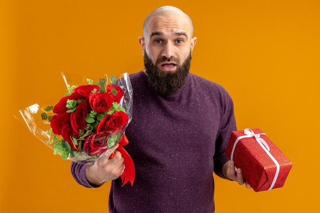 Junger bärtiger mann, der strauß der roten rosen und ein geschenk hält, das kamera überblickte, überraschte valentinstagkonzept, das über orange hintergrund steht