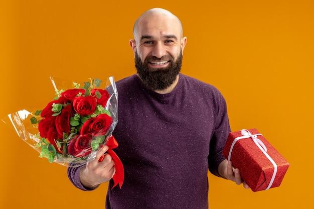 Junger bärtiger mann, der strauß roter rosen und ein geschenk glücklich und fröhlich lächelnd breit valentinstagskonzept hält, das über orange wand steht