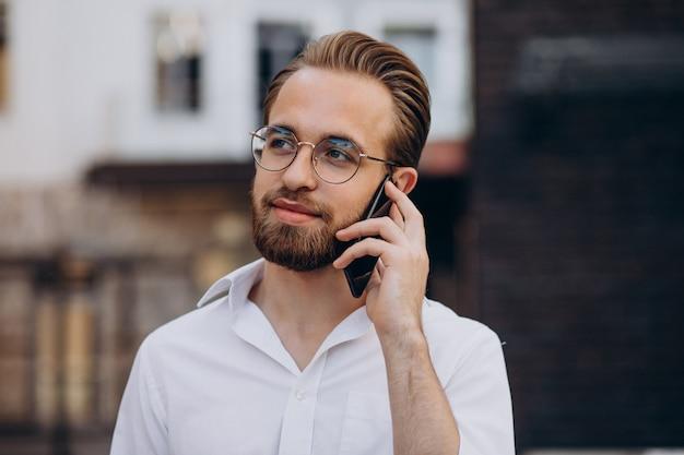 Junger bärtiger mann, der telefon benutzt und auf die straße geht