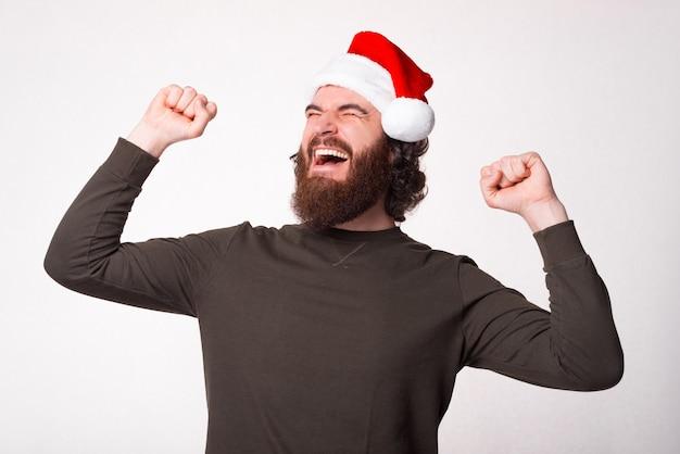 Junger bärtiger mann, der weihnachtsmannhut trägt und mit fäusten oben feiert