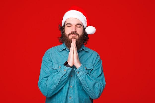 Junger bärtiger mann, der weihnachtsmütze trägt, hält seine hände, die über rotem hintergrund beten