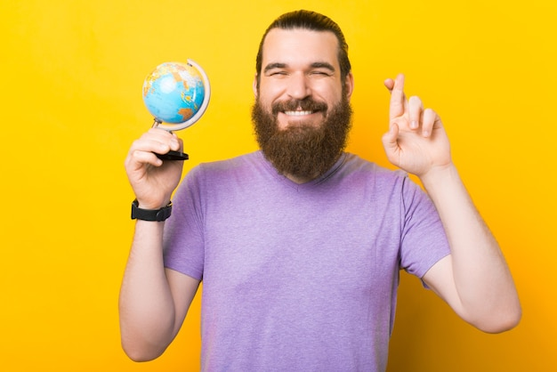 Junger bärtiger mann hält einen kleinen globus und kreuzt die finger.