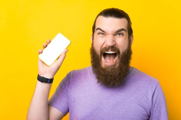 Junger bärtiger mann hält sein telefon und schreit in die kamera.