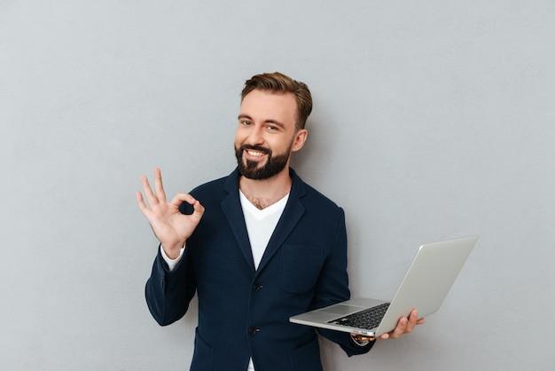 Junger bärtiger mann im anzug, der kamera schaut, während laptop-computer isoliert hält
