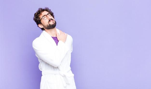 Junger bärtiger mann im bademantel, der sich müde, gestresst, ängstlich, frustriert und depressiv fühlt und unter rücken- oder nackenschmerzen leidet