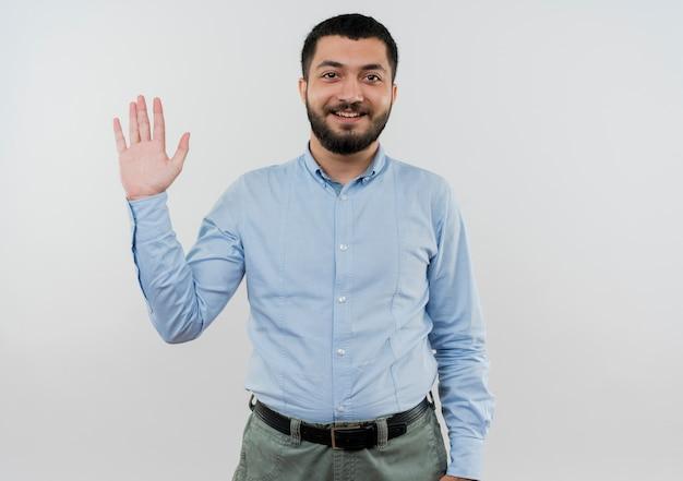 Junger bärtiger mann im blauen hemd, das mit lächelnder hand winkt