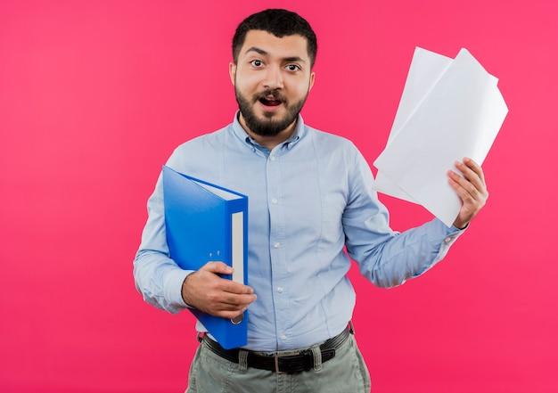 Junger bärtiger mann im blauen hemd, das ordner und leere seiten glücklich und aufgeregt hält