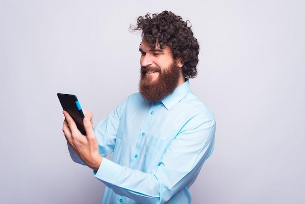 Junger bärtiger mann im blauen hemd, das tablette für arbeit verwendet