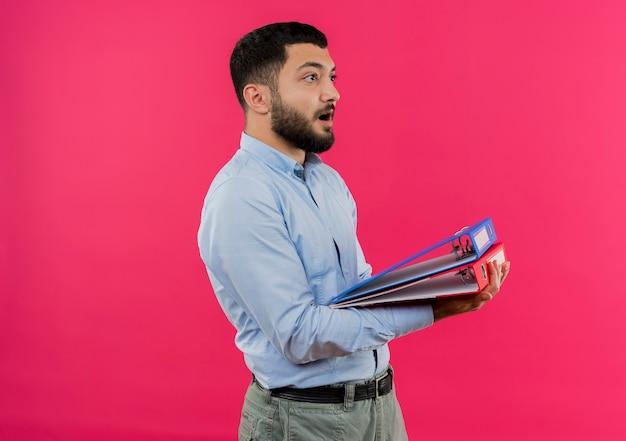 Junger bärtiger mann im blauen hemd, der laptop hält, der beiseite schaut, erstaunt und überrascht