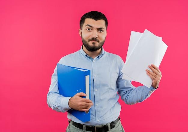 Junger bärtiger mann im blauen hemd, der ordner und leere seiten hält, missfiel