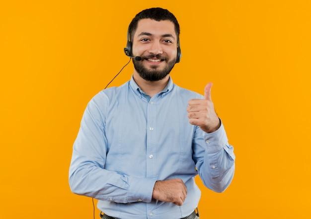 Junger bärtiger mann im blauen hemd mit kopfhörern mit dem lächelnden mikrofon, das daumen oben zeigt