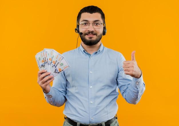Junger bärtiger mann im blauen hemd mit kopfhörern mit mikrofon, das bargeld hält, zeigt daumen hoch, die mit glücklichem gesicht lächeln