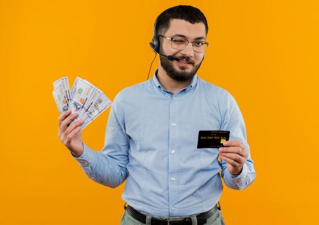 Junger bärtiger mann im blauen hemd mit kopfhörern mit mikrofon, der bargeld hält, das lächelnde und zwinkernde kreditkarte zeigt