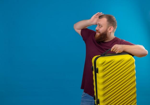 Junger bärtiger mann im braunen t-shirt, der reisekoffer hält, der verwirrt und ängstlich beiseite schaut
