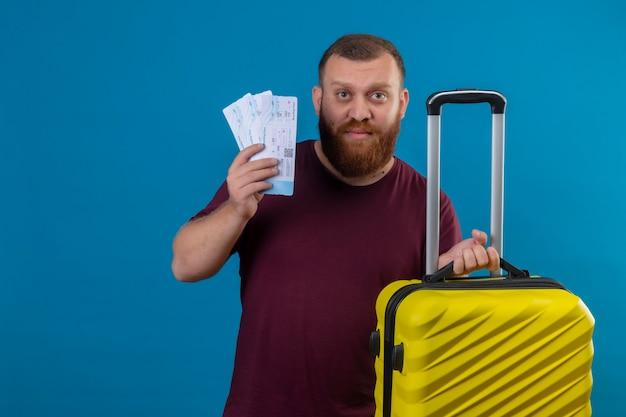 Junger bärtiger mann im braunen t-shirt, der reisekoffer und flugtickets hält kamera mit traurigem ausdruck auf gesicht betrachtet
