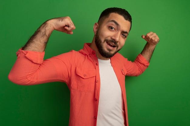 Junger bärtiger mann im orangefarbenen hemd ballt die fäuste glücklich und aufgeregt und freut sich über seinen erfolg, der über grüner wand steht