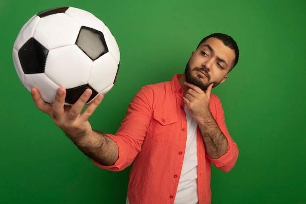 Junger bärtiger mann im orangefarbenen hemd, das fußball hält, der es faszinierte, das über grüner wand steht