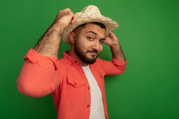 Junger bärtiger mann im orangefarbenen hemd und im sommerhut, der zuversichtlich lächelnd schaut, seinen hut stehend über grüner wand fixierend