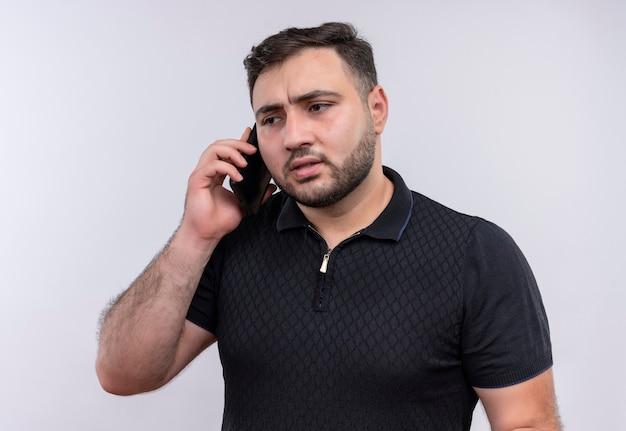 Junger bärtiger mann im schwarzen hemd, das auf handy mit ernstem gesicht spricht