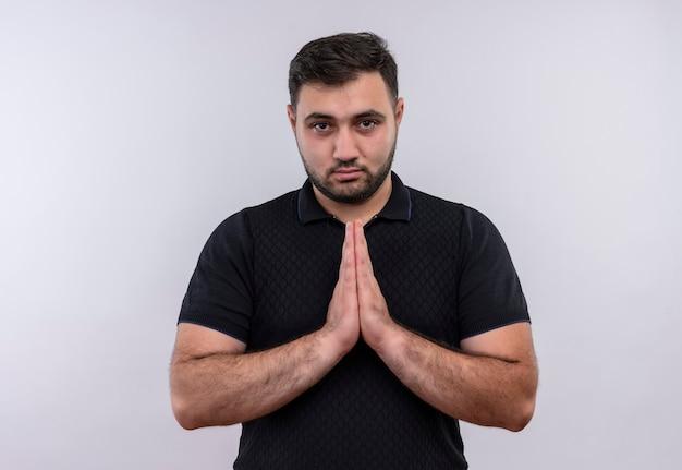 Junger bärtiger mann im schwarzen hemd, das hände zusammen mit hoffnungsausdruck auf gesicht hält