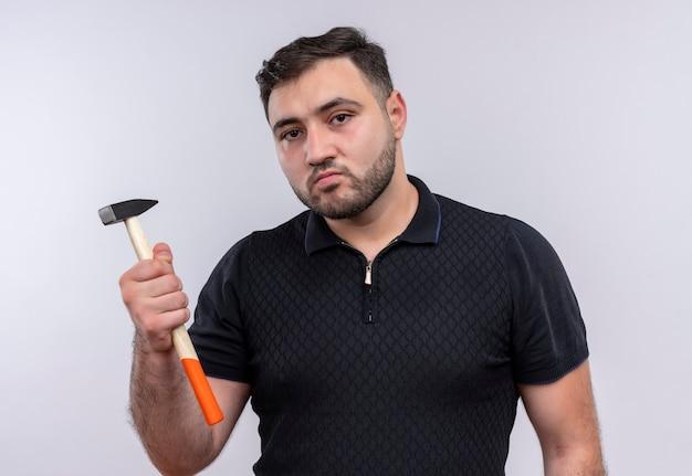 Junger bärtiger mann im schwarzen hemd, das hammer hält kamera mit ernstem gesicht betrachtet