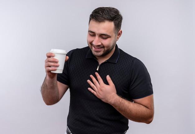 Junger bärtiger mann im schwarzen hemd, das kaffeekappe hält, die positiv und glücklich lächelt