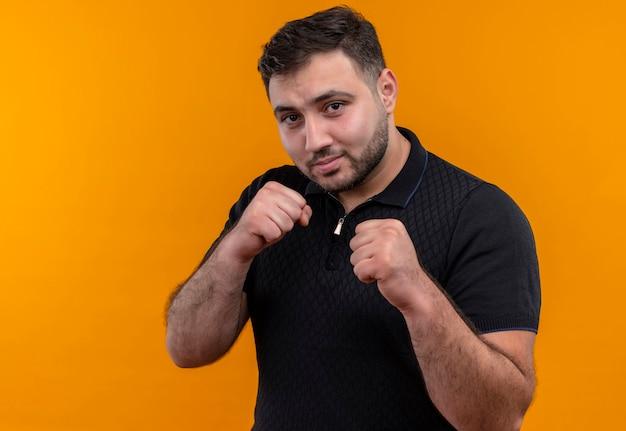 Junger bärtiger mann im schwarzen hemd, das kamera betrachtet, die wie eine boxer-faust ballt